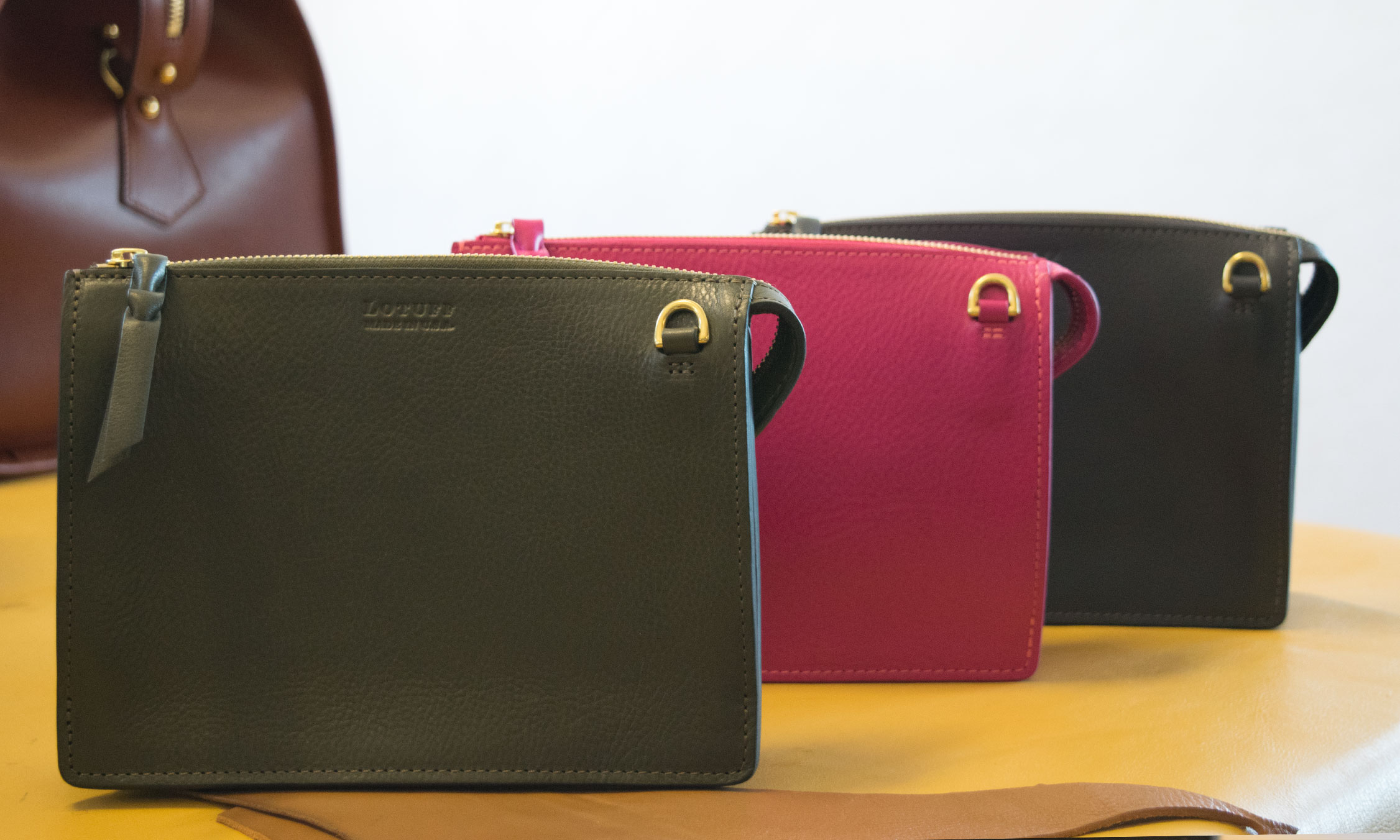 Lotuff Leather Tripp handbag in olive green, magenta, and elephant.