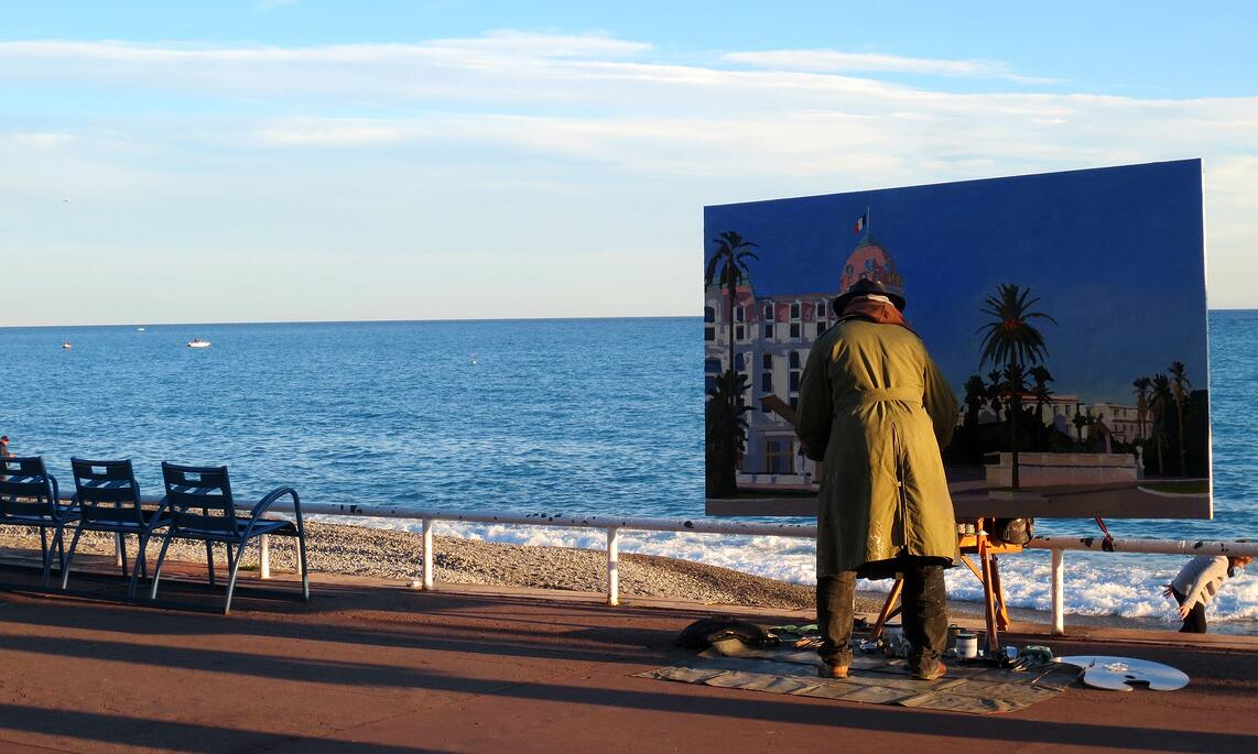 Street artist painting the Hotel Negresco on the Promenade des Anglais in Nice, France