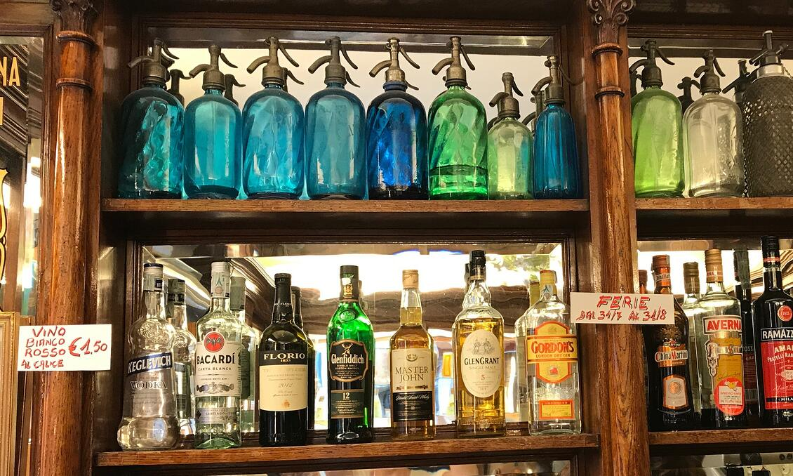 Colored glass bottles behind a bar in Florence